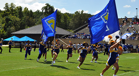 Cheerleaders running with banner flags