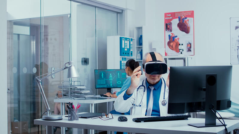 Senior physician using VR glasses in modern private clinic
