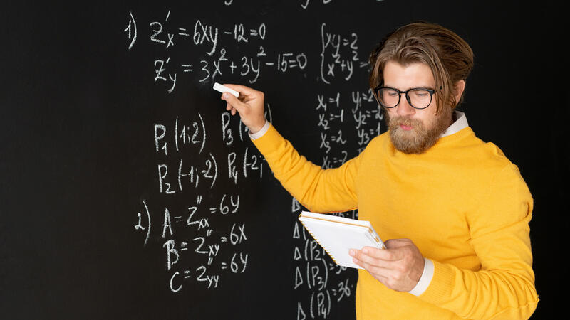 Math Education - Serious teacher pointing at equation on blackboard with piece of chalk
